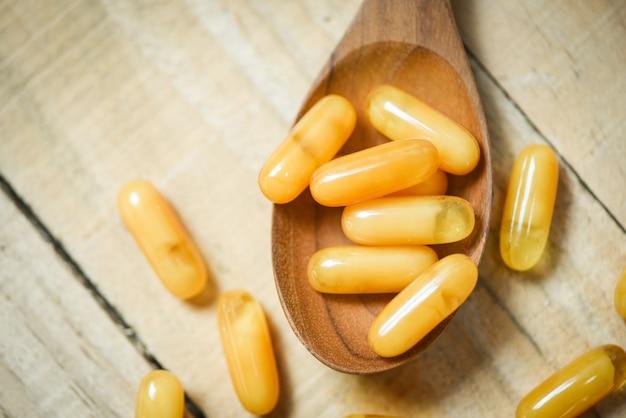 Cápsulas de jalea real en cuchara de madera y mesa de madera / medicina de cápsula amarilla o alimentos complementarios de la naturaleza para la salud