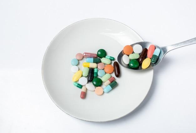 Cápsulas y píldoras coloridas en la placa blanca con la cuchara. salud