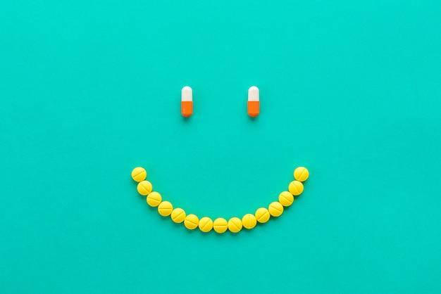 Cápsulas y píldoras dispuestas en la cara sonriente.
