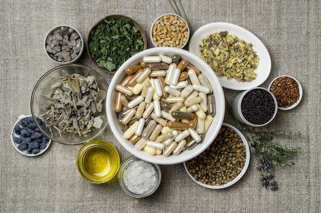 Cápsulas con suplementos dietéticos, minerales, aceite y hierbas en platos