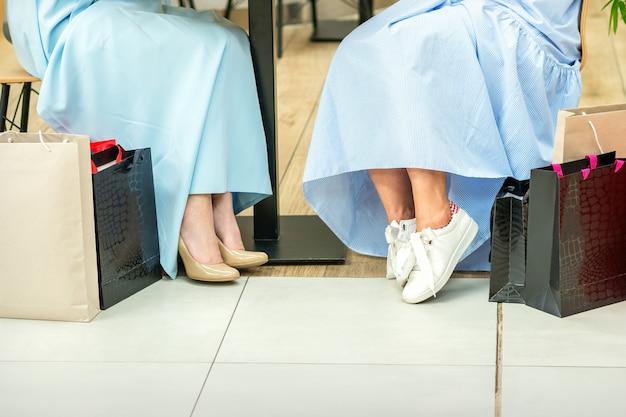 Captura de cultivos de piernas femeninas con bolsas de compras en la cafetería del centro comercial