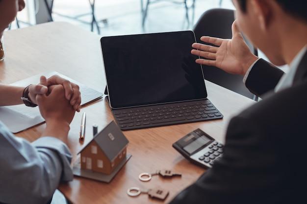 Captura recortada del agente inmobiliario discutiendo junto con su cliente en la reunión.