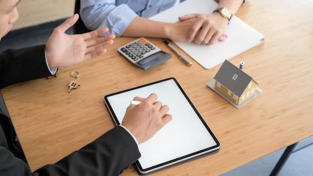 Captura recortada del agente de préstamos de la cámara utilizando una tableta de pantalla en blanco mientras se presenta al cliente