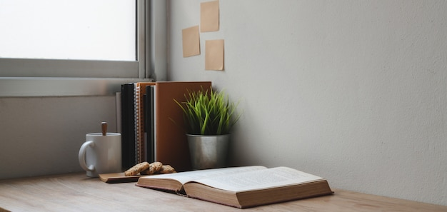 Captura recortada de cómodo lugar de trabajo con libros y material de oficina en mesa de madera