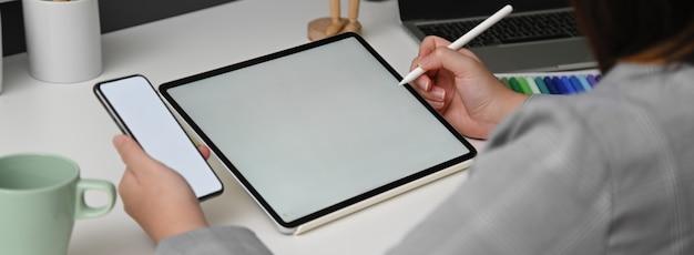 Captura recortada de una diseñadora que trabaja con una tableta simulada mientras busca información en el teléfono inteligente