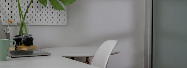 Captura recortada del diseño interior minimalista de la oficina en casa con mesa de trabajo blanca