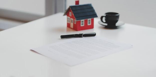 Captura recortada del documento del acuerdo de préstamo hipotecario con un modelo de casa pequeña