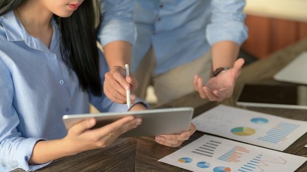 Captura recortada de dos empresarios informando sobre su proyecto en la mesa de madera