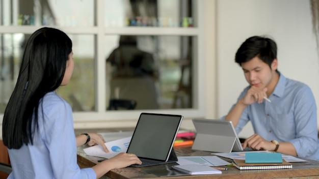 Captura recortada de dos empresarios que se centran en su proyecto mientras están sentados uno frente al otro
