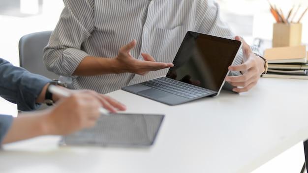 Captura recortada de dos empresarios que consultan sobre su trabajo con tabletas digitales