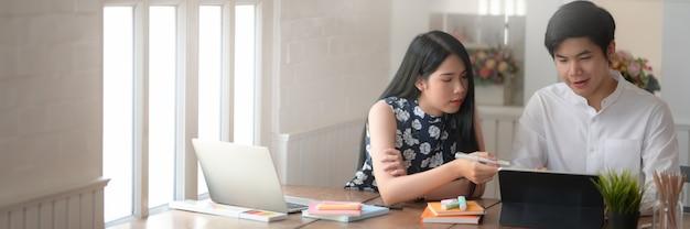 Captura recortada de dos estudiantes universitarios que consultan sobre su proyecto en un lugar de trabajo cómodo