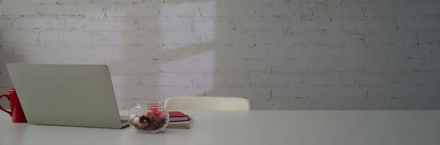 Captura recortada del elegante espacio de trabajo con computadora portátil, cuadernos, taza de café y espacio de copia en la mesa blanca