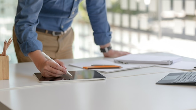Captura recortada del empresario escribiendo en tableta digital mientras lee el archivo del documento