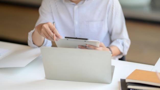 Captura recortada del empresario masculino que analiza el archivo del documento con una computadora portátil y suministros de oficina