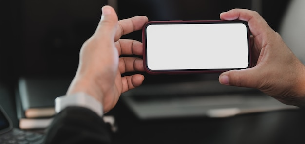 Captura recortada del empresario profesional con pantalla en blanco en la oscura sala de oficina moderna