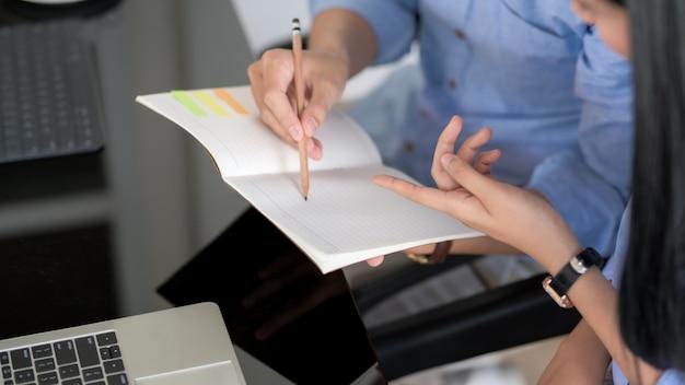 Captura recortada de empresarios discutiendo sobre su trabajo mientras mira en el cuaderno