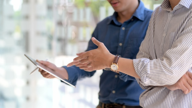 Captura recortada de empresarios informando sobre su trabajo mientras están parados en la oficina de pared de vidrio