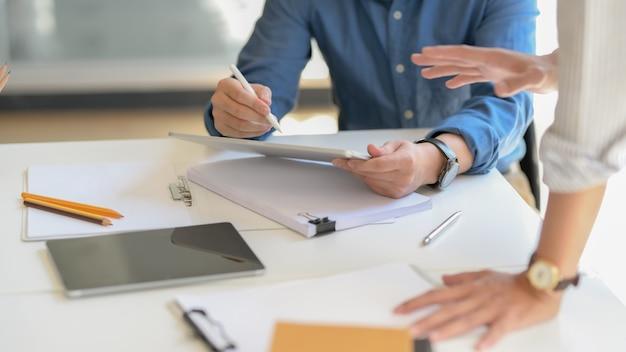 Captura recortada de empresarios informando sobre su trabajo con tableta digital y archivo de documentos