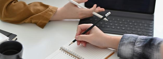 Captura recortada de empresarios que consultan sobre su proyecto en el escritorio de oficina blanco