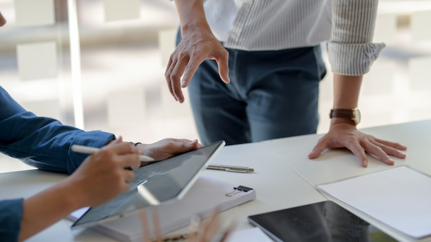 Captura recortada de empresarios que consultan sobre su proyecto con tableta digital y archivo de documentos