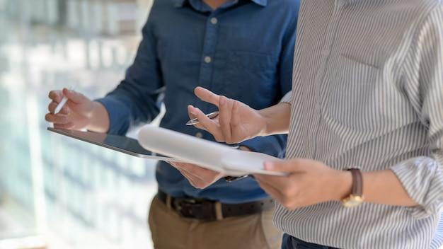 Captura recortada de empresarios que consultan sobre su trabajo con tableta digital y archivo de documentos