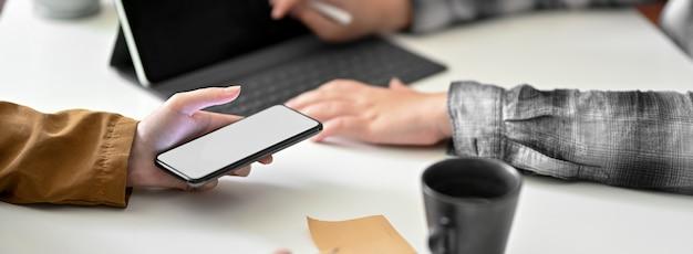 Captura recortada de empresarios que consultan sobre su trabajo con el teléfono inteligente en el escritorio de la oficina moderna