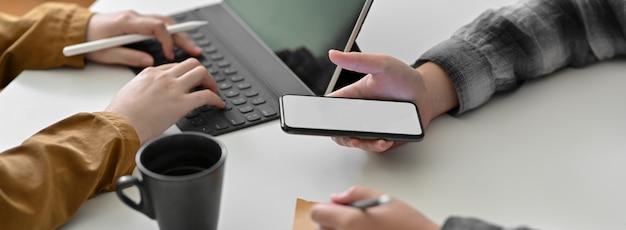 Captura recortada de empresarios que trabajan en tabletas y teléfonos inteligentes