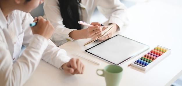 Captura recortada del equipo de jóvenes diseñadores que intercambian los conceptos de ideas juntos mientras usan una tableta simulada en la oficina moderna