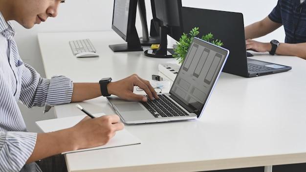 Captura recortada del equipo de programadores jóvenes mientras trabajan / concentrados en el trabajo en la oficina.