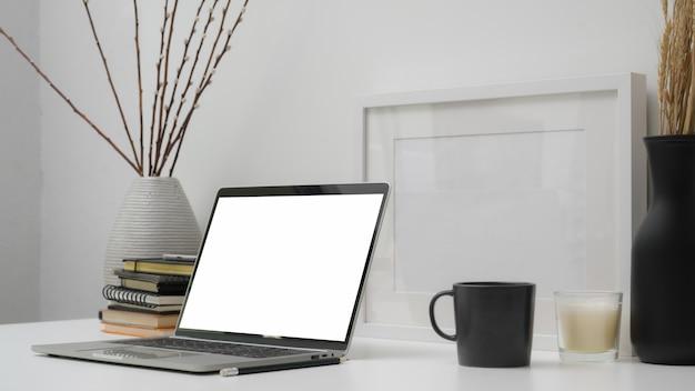 Captura recortada del espacio de trabajo con pantalla en blanco portátil, suministros de oficina y decoraciones en mesa blanca