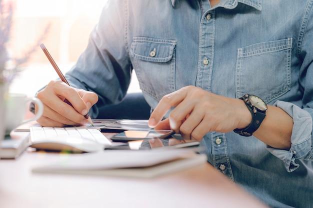 Captura recortada del hombre escribiendo y usando smartphone blanco sentado en la cafetería.