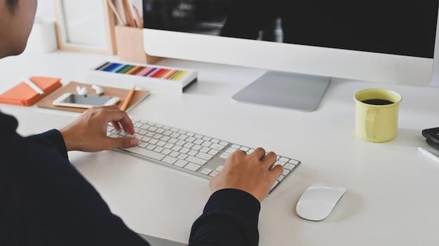 Captura recortada de hombre inteligente escribiendo en el teclado en frente del monitor de la computadora de pantalla en blanco negro y sentado en la mesa de trabajo moderna con cómodo lugar de trabajo