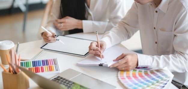 Captura recortada del joven diseñador profesional que trabaja en sus conceptos junto con una tableta simulada