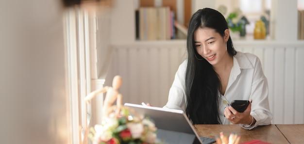 Captura recortada de una joven empresaria trabajando en su proyecto mientras usa el teléfono inteligente en una cómoda oficina