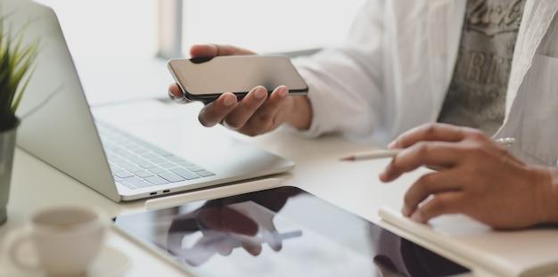 Captura recortada de joven freelance masculino tocando su teléfono inteligente en la oficina moderna