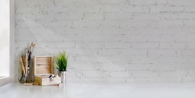 Captura recortada del lugar de trabajo minimalista del artista con herramientas de pintura en mesa blanca y pared de ladrillo blanco