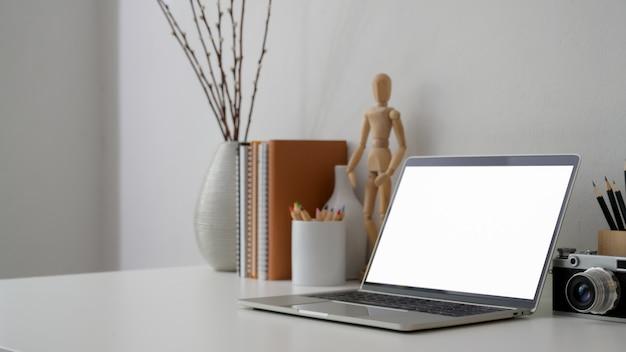 Captura recortada del lugar de trabajo con pantalla en blanco portátil, cámara y decoraciones