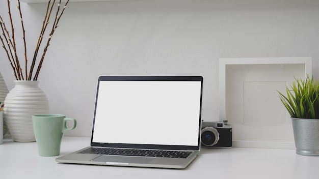 Captura recortada del lugar de trabajo con pantalla en blanco portátil, marco, decoraciones y cámara en escritorio blanco