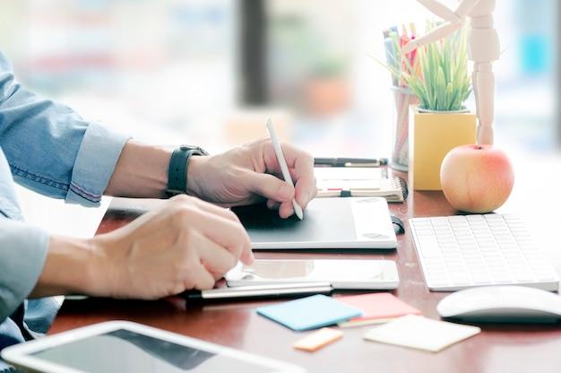 Captura recortada de la mano del hombre usando dibujo digital de pluma y trabajando con la computadora en el estudio.