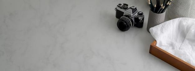 Captura recortada de una mesa de trabajo simple con cámara, papelería, suministros y espacio de copia