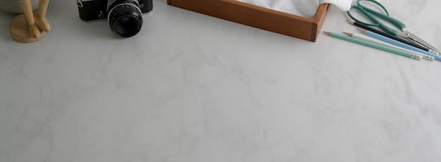 Captura recortada de una mesa de trabajo simple con cámara, suministros y espacio de copia