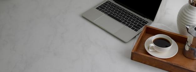 Captura recortada de mesa de trabajo simple con computadora portátil, taza de café en bandeja de madera y espacio de copia