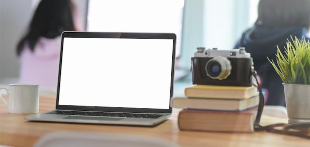Captura recortada de la moderna sala de oficina con computadora portátil con pantalla en blanco abierta, cámara y suministros de oficina