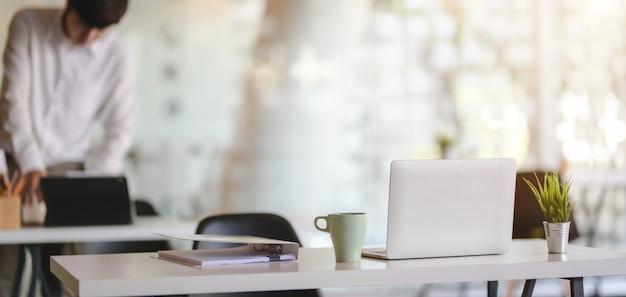 Captura recortada de la moderna sala de oficina con computadora portátil y suministros de oficina con fondo de entorno de oficina