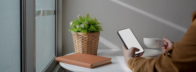 Captura recortada de mujer freelance relajante con maquetas de teléfonos inteligentes en casa