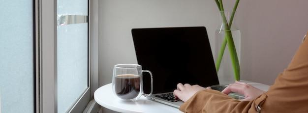 Captura recortada de mujer profesional independiente que trabaja con la computadora portátil en la mesa de centro círculo blanco