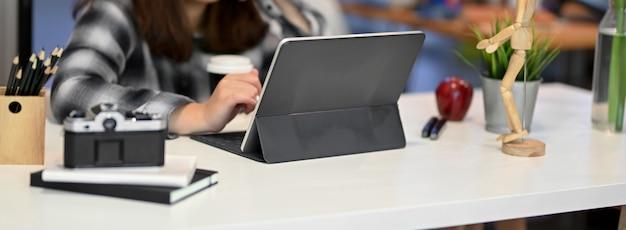 Captura recortada de mujer profesional independiente que trabaja con tableta digital, cámara y papelería en un lugar de trabajo mínimo
