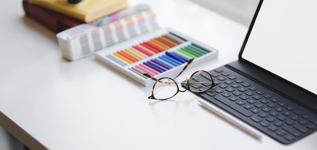 Captura recortada de la sala de oficina de diseño moderno con tableta digital de pantalla en blanco y suministros de oficina en mesa blanca