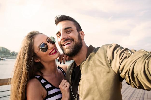 Capturando momentos brillantes. pares amorosos jovenes alegres que hacen el selfie en la cámara mientras que se coloca al aire libre.