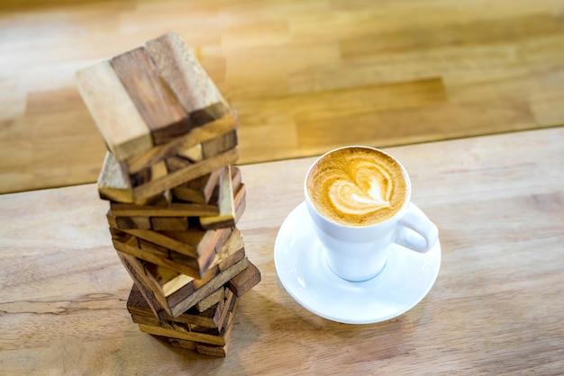 Capuchino de café de arte caliente en una taza y juguete de jenga en el fondo de la mesa de madera